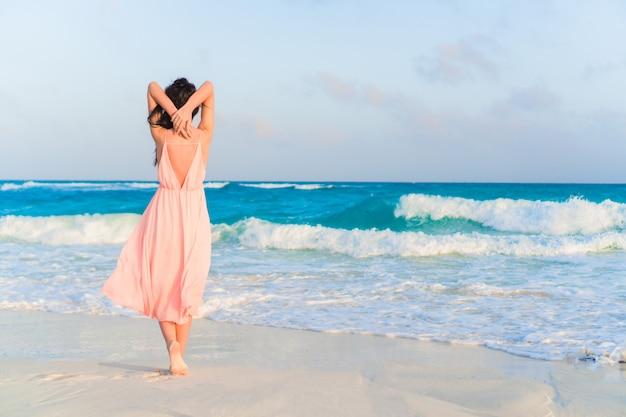 Молодая красивая женщина в платье на берегу моря на закате