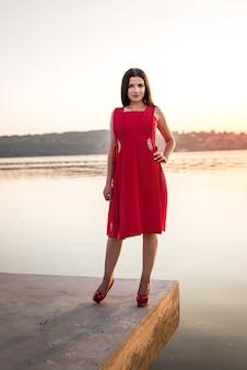 夕暮れ時の海岸でポーズをとってドレスの若い美しい女性