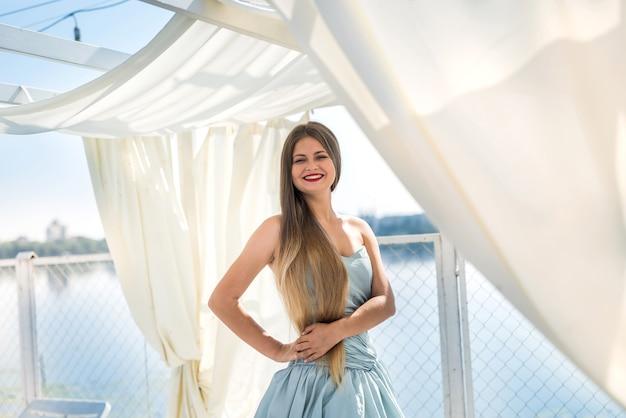 부두에 서있는 드레스에 젊은 아름 다운 여자
