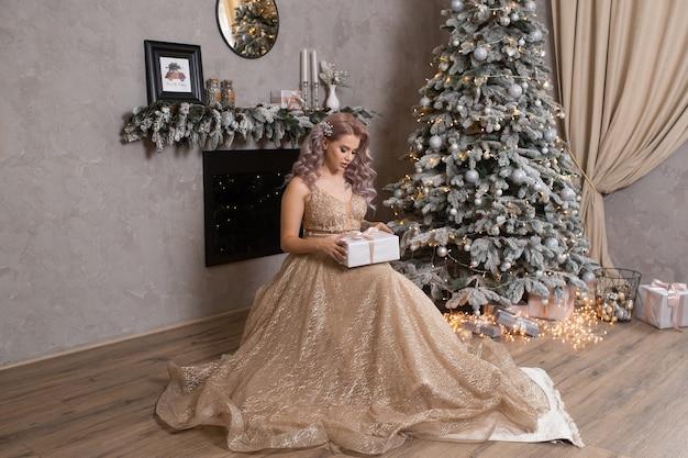 飾られたクリスマスツリーの近くのイブニングドレスの若い美しい女性