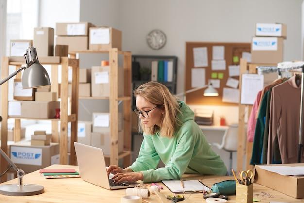 オフィスで働くテーブルでラップトップで入力する眼鏡の若い美しい女性