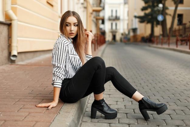 Молодая красивая женщина в модной одежде, сидя на обочине
