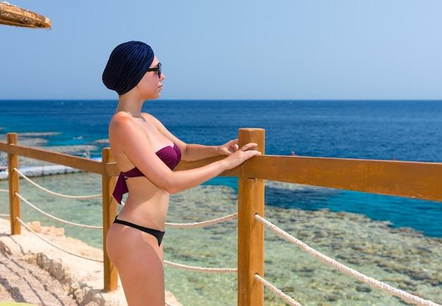 Молодая красивая женщина в женском тюрбане и солнцезащитных очках стоит перед деревянным забором с веревочными вставками на пляже и смотрит на красивое море
