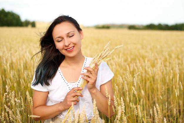 黄金の麦畑の若い美しい女性。夏、自由、暖かさ、収穫、農業の概念