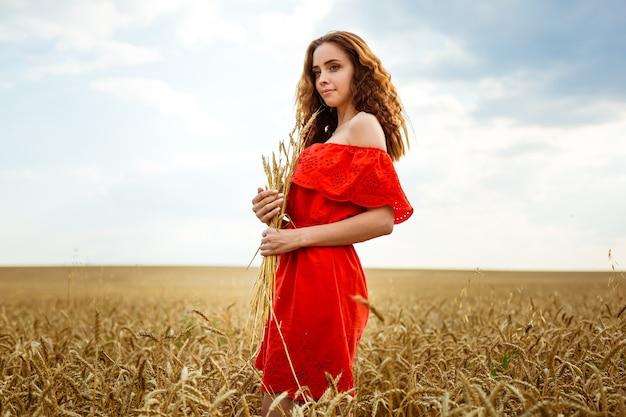 황금 밀밭에서 젊은 아름 다운 여자 필드 자연 b에서 인생을 즐기는 빨간 드레스에 행복 한 여자...
