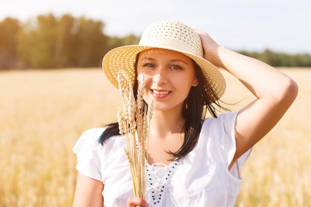 Молодая красивая женщина в золотом пшеничном поле