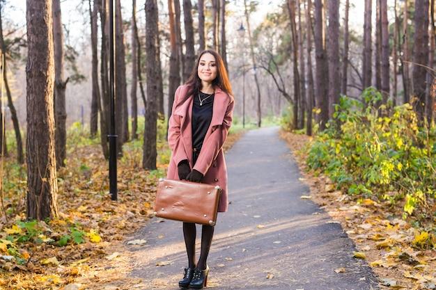 秋の自然の中で灰色のコートを着た若い美しい女性