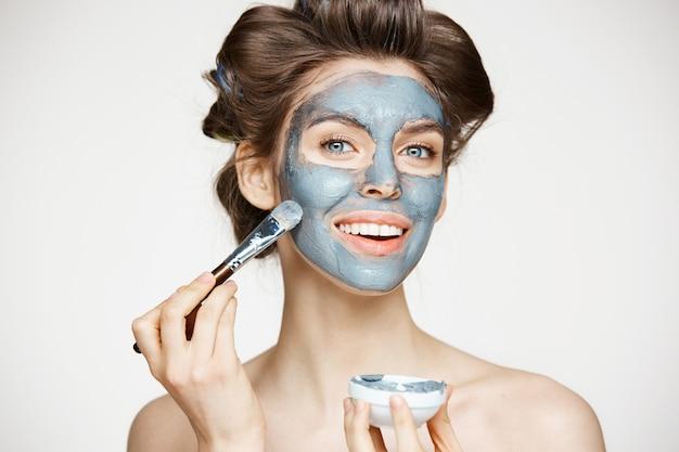 Молодая красивая женщина в бигуди, улыбаясь лицо с маком. уход за лицом. косметология и спа.