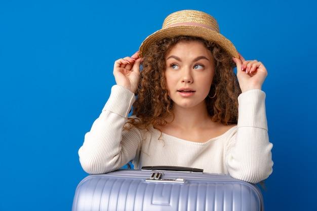 青い背景のスーツケースと休暇で帽子の若い美しい女性