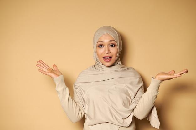 ヒジャーブの若い美しい女性は驚きと驚きを表現する正面を見て