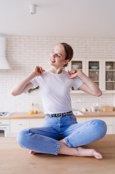 ジーンズと t シャツのキッチン テーブルでポーズをとる若い美しい女性