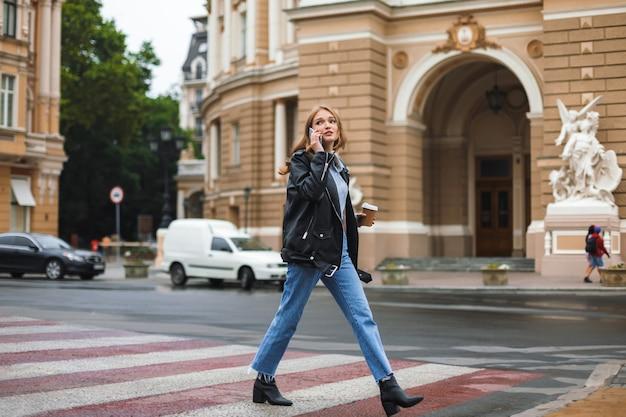 가죽 재킷과 청바지에 젊은 아름 다운 여자 커피 한잔 들고 아늑한 도시 거리를 걷는 동안 핸드폰에 손에 이야기