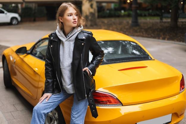 思慮深く黄色のスポーツカーに寄りかかって革のジャケットの若い美しい女性