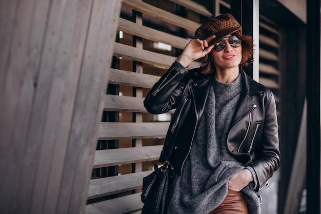 通りの外の革のジャケットの若い美しい女性