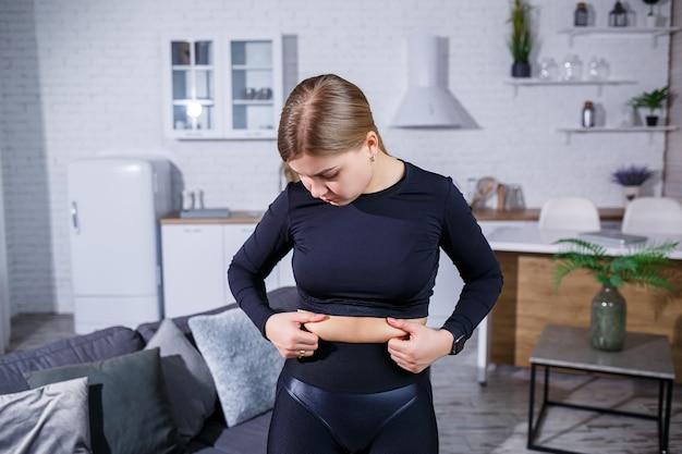 Молодая красивая женщина в леггинсах и топе показывает складку на животе. здоровый образ жизни. женщина занимается спортом дома. борьба с лишним весом в домашних условиях