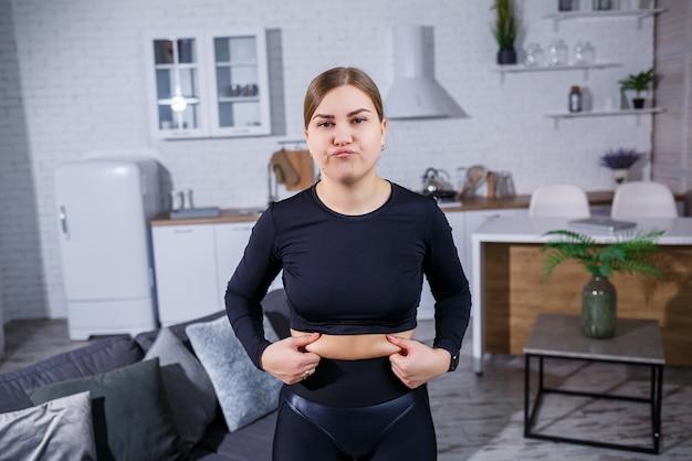レギンスとトップの若い美しい女性は、腹に折り目を示しています。健康的な生活様式。女性は家でスポーツに行く。自宅で太りすぎと戦う