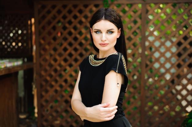 公園内の道を歩く長い黒のイブニングドレスの若い美しい女性。ゴージャスな美しい女性のファッションスタイルの肖像画