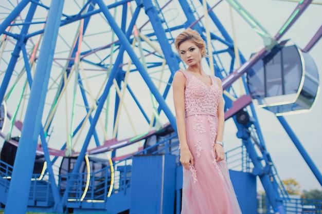 公園の長いピンクのイブニングドレスの散歩道の若い美しい女性。観覧車の近くの屋外でゴージャスな美しい少女のファッションスタイルの肖像画