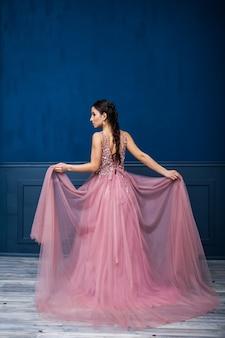長いスタイリッシュなイブニングドレスの若い美しい女性