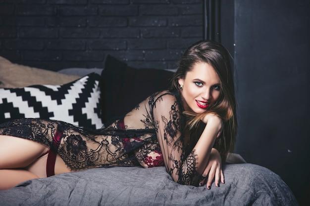 ベッドのある寝室で豪華なランジェリーファッショナブルなブルネットの若い美しい女性