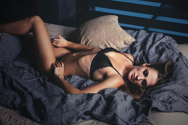 Молодая красивая женщина в роскошном нижнем белье модная брюнетка в спальне с кроватью