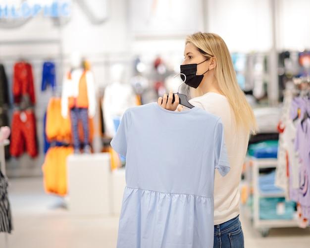 ショッピングセンターのマスクの若い美しい女性は手で作られた美しいドレスを保持しています