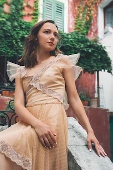 구시가지의 역사적인 유럽 거리에서 중세 드레스를 입은 젊은 아름다운 여성