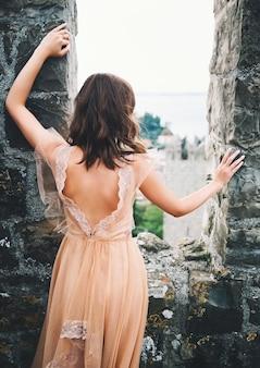 旧市街の歴史的なヨーロッパの通りに中世のドレスを着た若い美しい女性