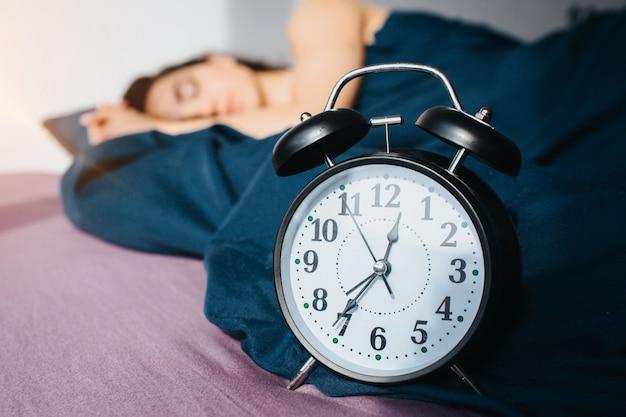 Молодая красивая женщина в постели утром у себя дома. женская модель спит одна, спокойная и мирная. женщина размыта. учение сосредоточено на часах.