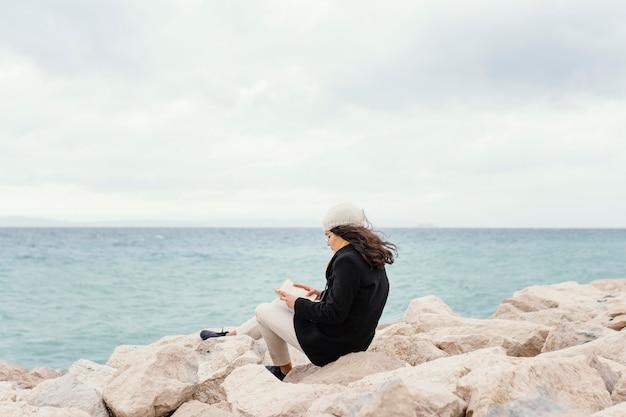 自然の読書の若い美しい女性