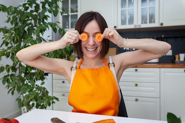 オレンジ色のエプロンの若い美しい女性がテーブルに座って、楽しんで、目の上のニンジン、家庭で野菜を調理、キッチンの背景、水平、テキストのコピースペース