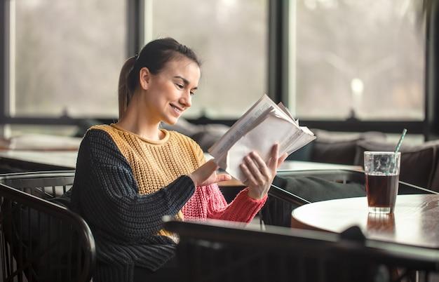 Молодая красивая женщина в оранжевом свитере читает интересную книгу в кафе