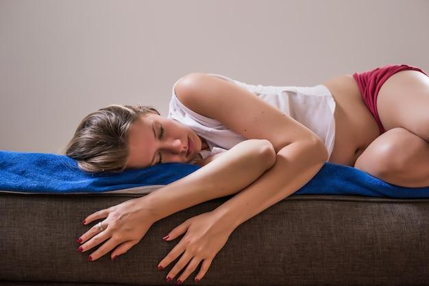 若い美しい女性の痛みを伴う表現苦しんで苦しんで月経周期の痛みを悲しい家のソファソファーtummy cramp女性の健康の概念です。月経痙攣、過度のガス、手術後の腹痛