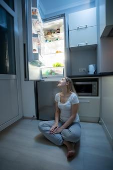 キッチンの床に座って、オープン冷蔵庫を見ているパジャマの若い美しい女性