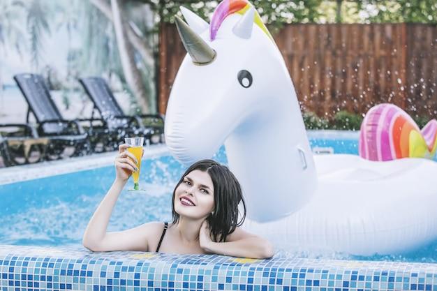 풍선 유니콘과 칵테일 수영장에서 분홍색 수영복에 젊은 아름 다운 여자