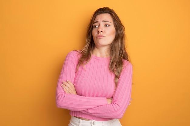 ピンクのトップの若い美しい女性は、腕を組んで不機嫌に脇を見て