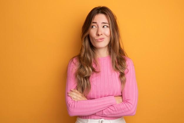 オレンジ色の上に立っている失望した表情で苦い口を作る脇を見てピンクのトップの若い美しい女性