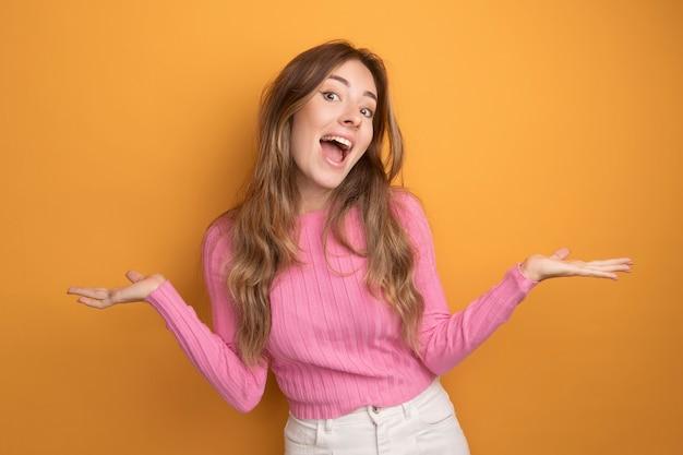 ピンクのトップの若い美しい女性がカメラを見て幸せで興奮して腕を横に広げます