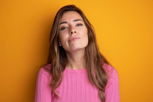 オレンジの上に立っている自信を持って表情でカメラを見てピンクのトップの若い美しい女性
