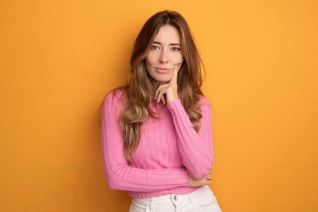 주황색 배경 위에 서서 턱에 손을 대고 자신감 넘치는 표정으로 카메라를 바라보는 분홍색 상의를 입은 젊은 미녀