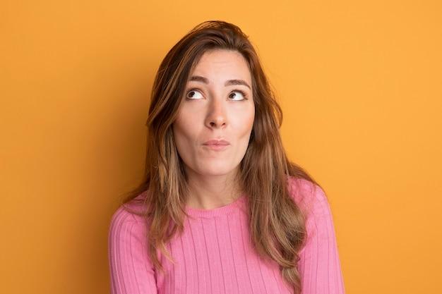 オレンジ色の上に立って困惑して見上げるピンクのトップの若い美しい女性
