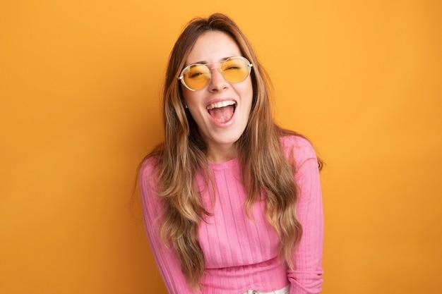 オレンジ色の上に立って笑って幸せで興奮した眼鏡をかけているピンクのトップの若い美しい女性