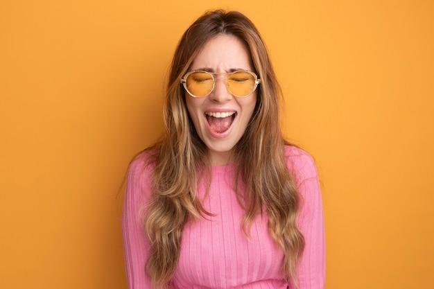 オレンジ色の上に立って幸せで興奮した叫び声の眼鏡をかけているピンクのトップの若い美しい女性