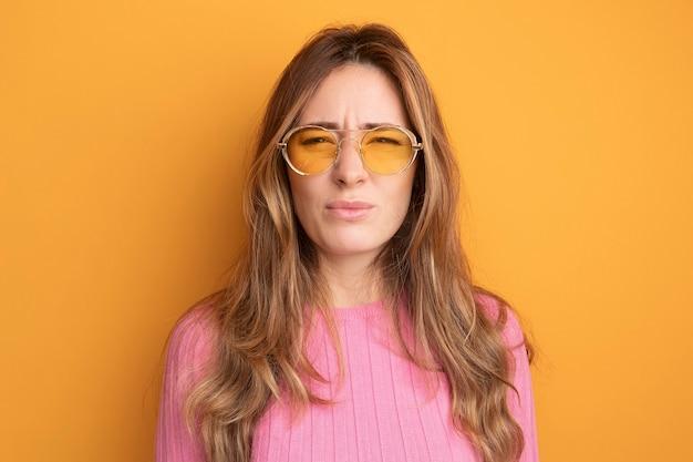 オレンジ色の上に立って眉をひそめているカメラを見て眼鏡をかけているピンクのトップの若い美しい女性