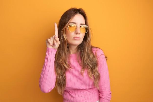人差し指を示す深刻な顔で見上げる眼鏡をかけているピンクのトップの若い美しい女性
