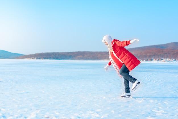 Молодая красивая женщина в красном пальто и фигурных коньках стоит на замерзшем море