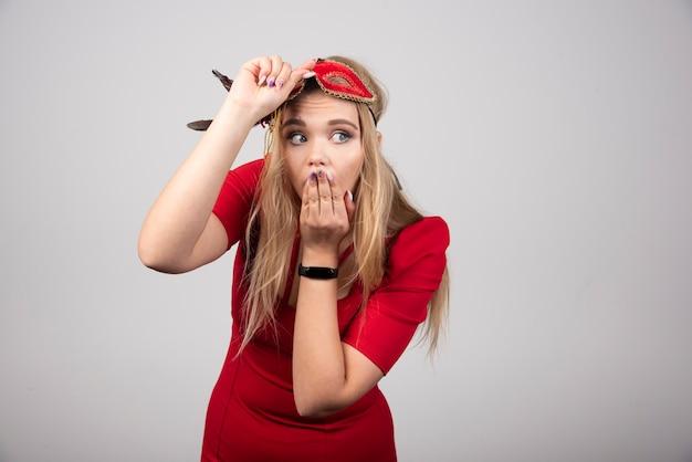 びっくりする赤いマスクの若い美しい女性。