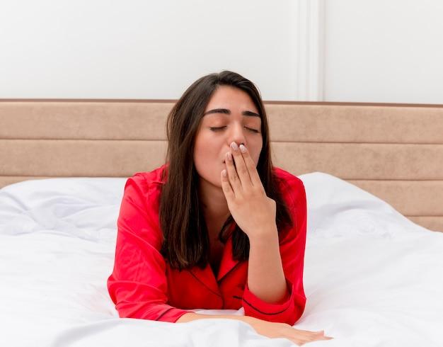 Молодая красивая женщина в красной пижаме, лежа на расслабляющей кровати, хочет спать, зевая в домашнем интерьере на светлом фоне