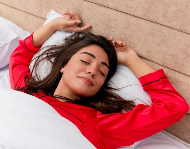 ベッドでリラックスして赤いパジャマの若い美しい女性