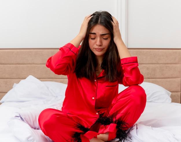 Молодая красивая женщина в красной пижаме, расслабляясь в постели